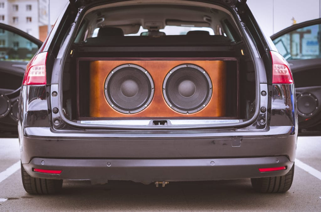 Car with its trunk open with two subwoofers showing how subwoofers work